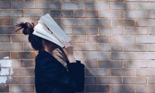 Ragazza che si copre il volto con un libro