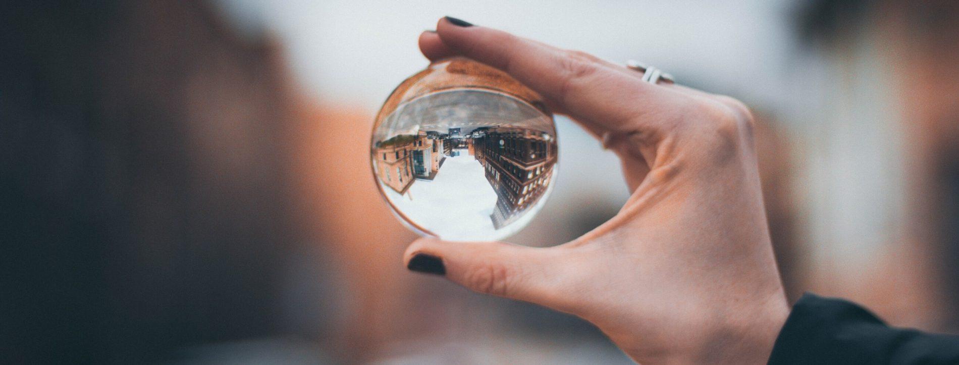 Foto di una mano che regge una sfera di vetro