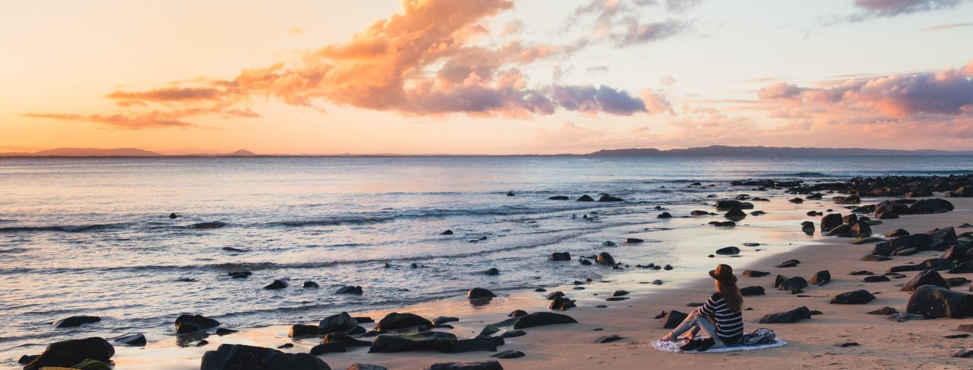 Immagine di una ragazza che guarda il mare da una spiaggia