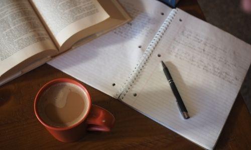 Immagine di una tazza di caffè accanto ad un quaderno