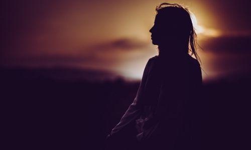 Foto di un ragazza che osserva un tramonto pensierosa