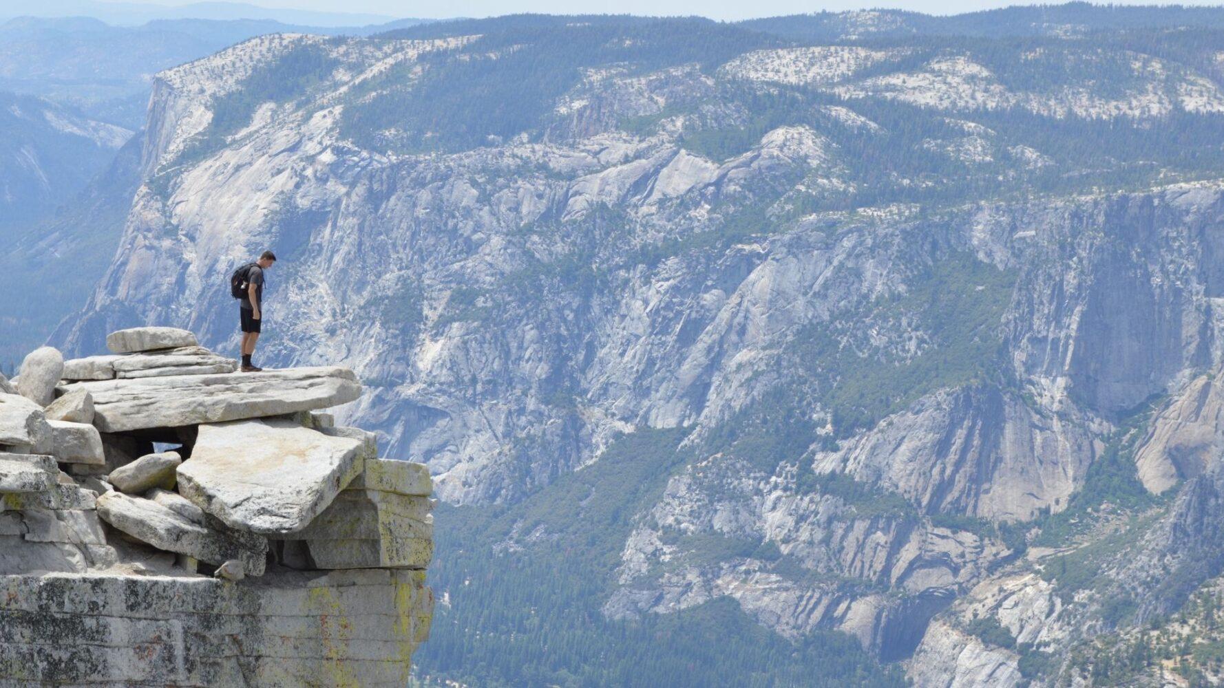 Ragazzo in cima ad una montagna che osserva il vuoto