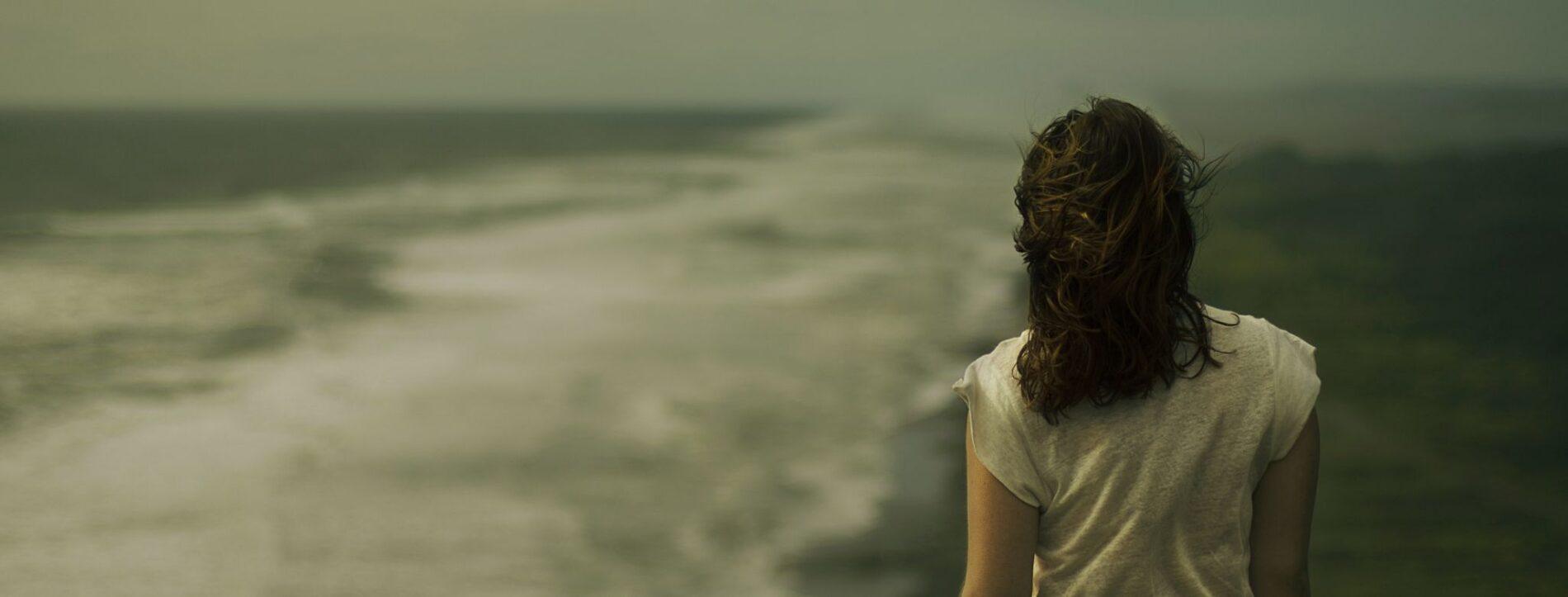 Immagine di una ragazza di spalle che guarda il mare