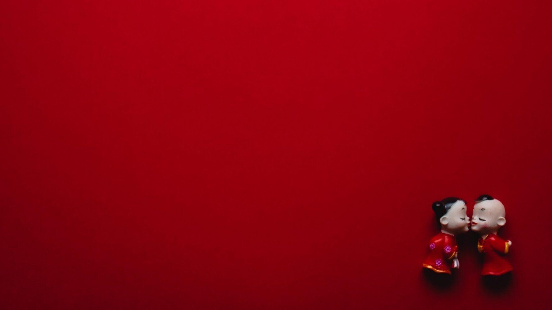Due bamboline che si baciano su sfondo rosso