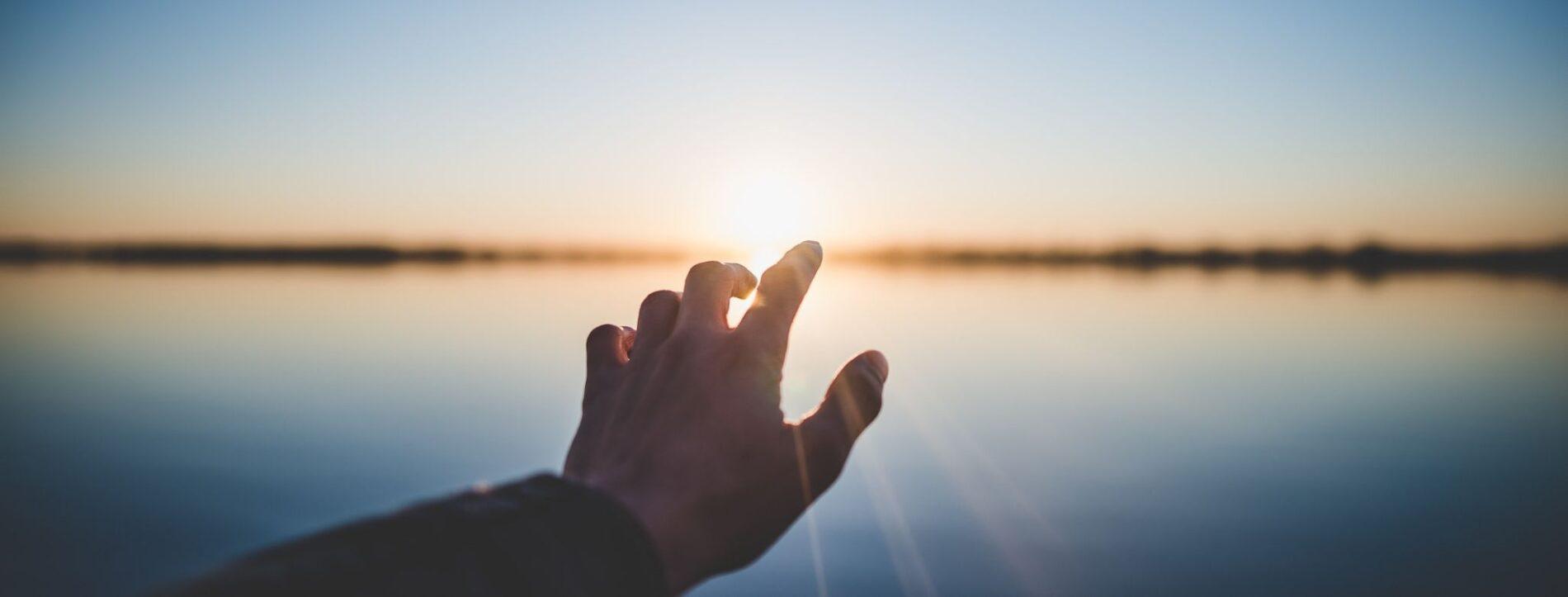 Foto di una mano che punta verso il sole