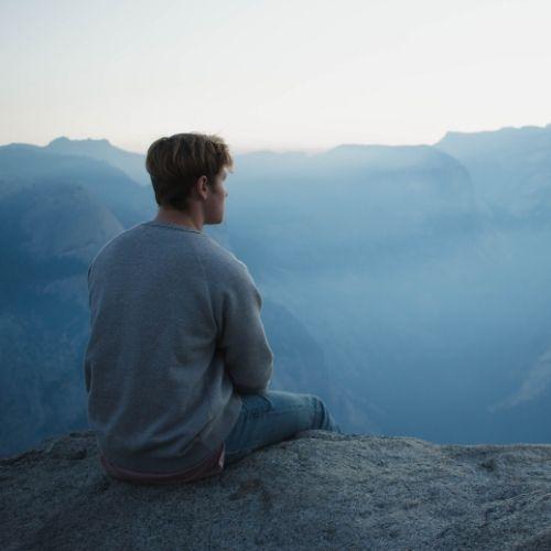 Foto di un ragazzo che medita in cima ad una montagna