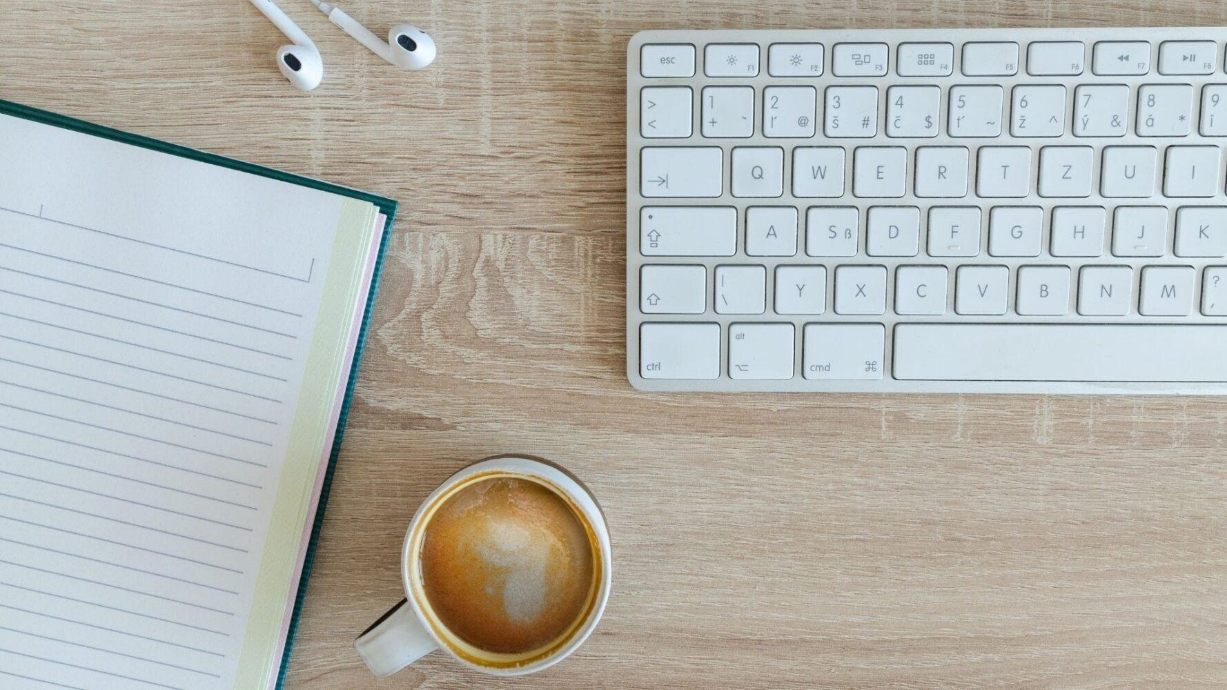 Immagine di una scrivania con un caffè ed un libro